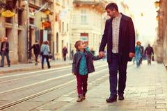 Père à la mode et fils marchant dans la vieille rue de ville Photo libre de droits