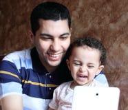 Père égyptien arabe heureux de sourire avec la fille prenant le selfie Photographie stock libre de droits