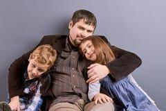 Père étreignant son fils et fille Photographie stock