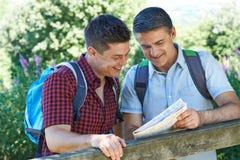Père With Adult Son regardant la carte sur la hausse dans la campagne Toge Photo libre de droits