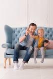 Père affectueux gai tenant une main de sa fille  Photographie stock libre de droits