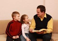 Père affichant un livre pour des enfants Photographie stock