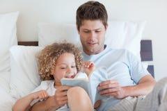 Père affichant une histoire pour l'enfant Photographie stock libre de droits