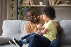 Père africain chatouillant le petit fils adorable ayant l'amusement à la maison images stock
