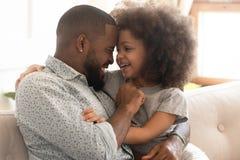 Père africain heureux et liaison mignonne de fille d'enfant embrassant rire images libres de droits