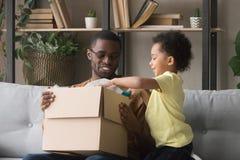 Père africain heureux et petit colis d'ouverture de fils à la maison photographie stock libre de droits