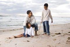 Père afro-américain et deux enfants sur la plage photographie stock