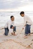 Père afro-américain et fils jouant sur la plage photographie stock libre de droits