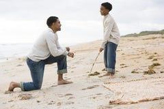 Père afro-américain et fils jouant sur la plage image libre de droits