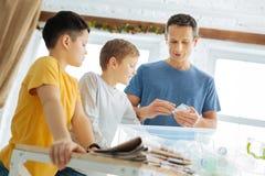 Père agréable enseignant à ses fils comment réutiliser des déchets image libre de droits