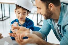 Père agréable parlant au sujet du modèle de la maison 3D Photographie stock