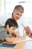Père aidant son fils avec son travail photo stock