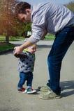 Père aidant son fils pour les premières étapes Image libre de droits