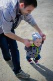 Père aidant son fils pour les premières étapes Image stock