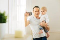 Père aimable prenant des photos avec un bébé tout en se tenant près de la fenêtre Images stock