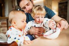 Père alimentant deux enfants en bas âge à la maison images stock