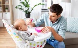 Père alimentant le bébé heureux dans le highchair à la maison image stock