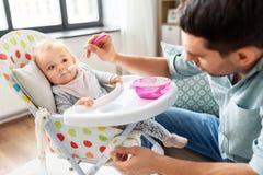 Père alimentant le bébé heureux dans le highchair à la maison images stock