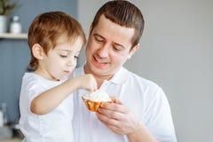 Père alimentant son petit fils dans la cuisine photographie stock libre de droits