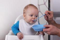 Père alimentant son petit fils mignon Photo stock