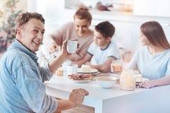 Père amical posant pour l'appareil-photo tout en mangeant avec la famille Images libres de droits