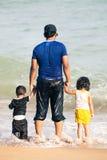 Père arabe avec deux enfants tenant des mains par la mer Photos stock
