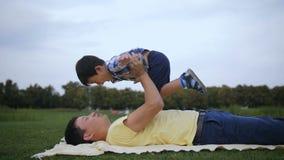 Père asiatique affectueux se soulevant vers le haut de son garçon riant banque de vidéos