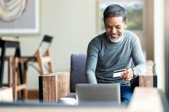 P?re asiatique de hippie barbu attirant ou vieil homme hispanique utilisant l'ordinateur portable et paiement par carte de cr?dit photographie stock