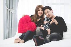 Père asiatique heureux de famille avec la fille de bébé jouant sur le lit images libres de droits