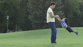 Père asiatique heureux tournant son fils mignon sur le pré banque de vidéos