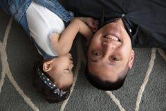 Père asiatique jouant sur le plancher avec la fille Images libres de droits