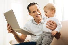 Père attentif aimable montrant une bande dessinée drôle à son enfant et sourire Photo stock