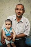 Père avec des enfants dans l'avant les murs typiques de boue de désert images stock