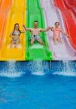 Père avec des filles sur la glissière tropicale Photographie stock libre de droits