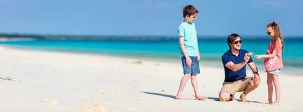 Père avec des gosses à la plage photos stock