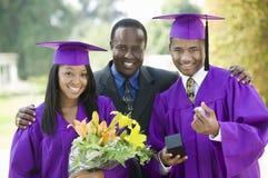 Père avec deux diplômés à l'extérieur Images stock