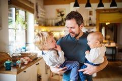 Père avec deux enfants en bas âge à la maison photos libres de droits