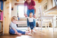Père avec deux enfants en bas âge à la maison Premières opérations photographie stock libre de droits