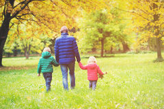 Père avec deux enfants marchant en nature de chute d'automne Photo stock