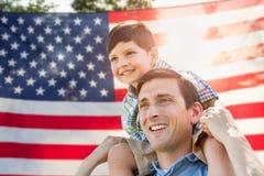 Père avec l'équitation de ferroutage de fils devant le drapeau américain images libres de droits