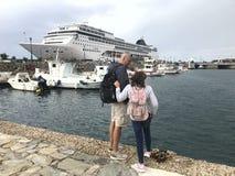 Père avec la fille dans le vieux port maritime sur l'île de Mykonos en Grèce dans la perspective d'un bateau de croisière images stock