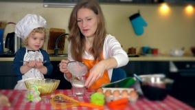 Père avec la fille mignonne d'enfant en bas âge préparant le gâteau dans la cuisine banque de vidéos