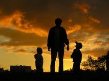 Père avec le coucher du soleil 2 d'enfants Photo stock