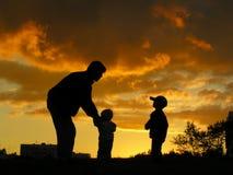 Père avec le coucher du soleil d'enfants Images stock