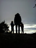 Père avec le coucher du soleil de montre d'enfants Images stock