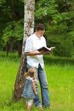 Père avec le descendant de chéri affichant la bible Photo libre de droits