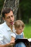 Père avec le descendant de chéri affichant la bible Image stock