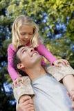 Père avec le descendant sur des épaules ayant l'amusement images stock