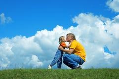Père avec le descendant sur l'herbe verte Images libres de droits