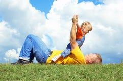 Père avec le descendant sur l'herbe verte Image stock